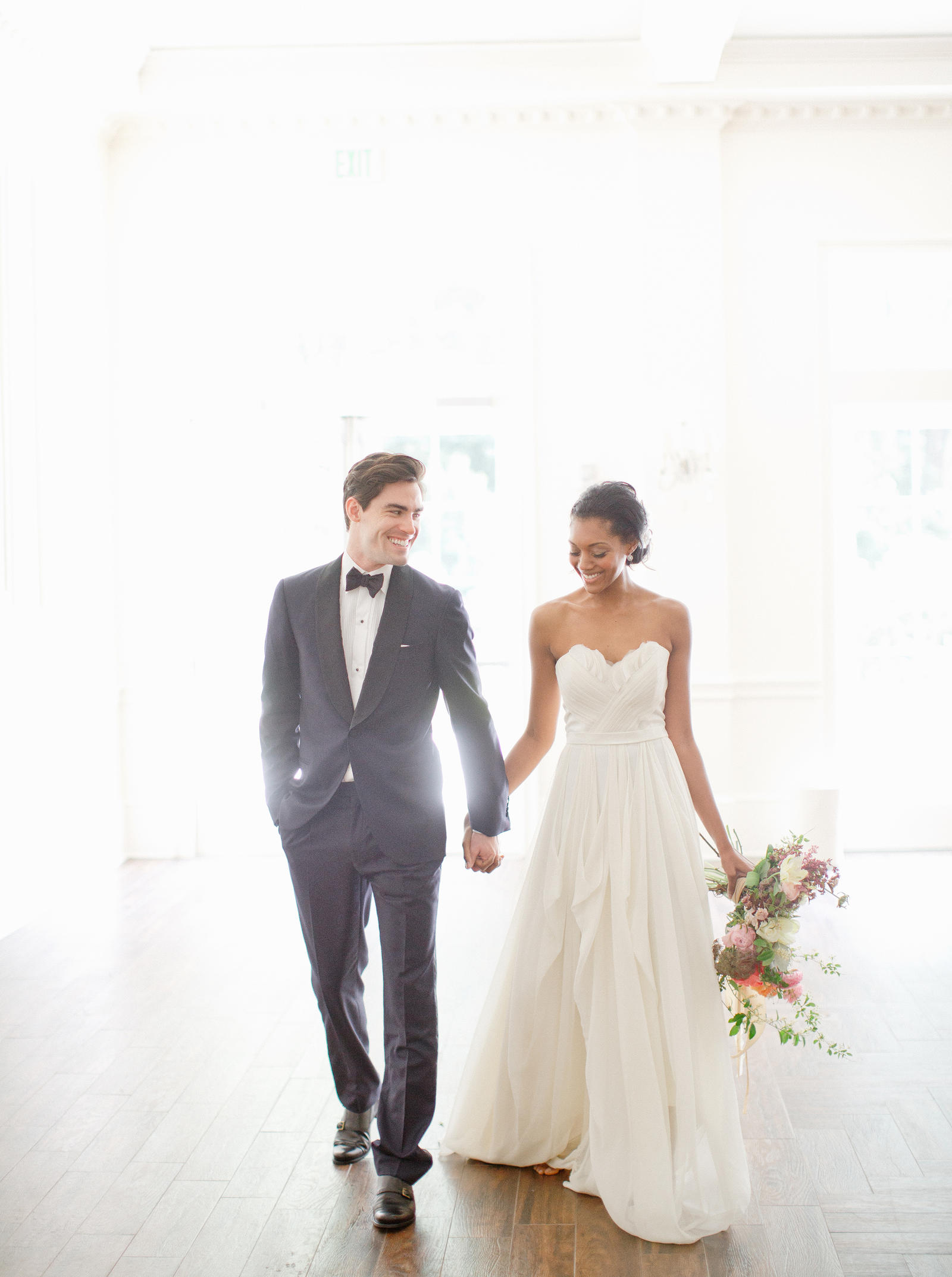 Editorial Photography | Atlanta, GA | A bride and groom walk together, hand in hand, with the sunlight streaming through the window behind them.