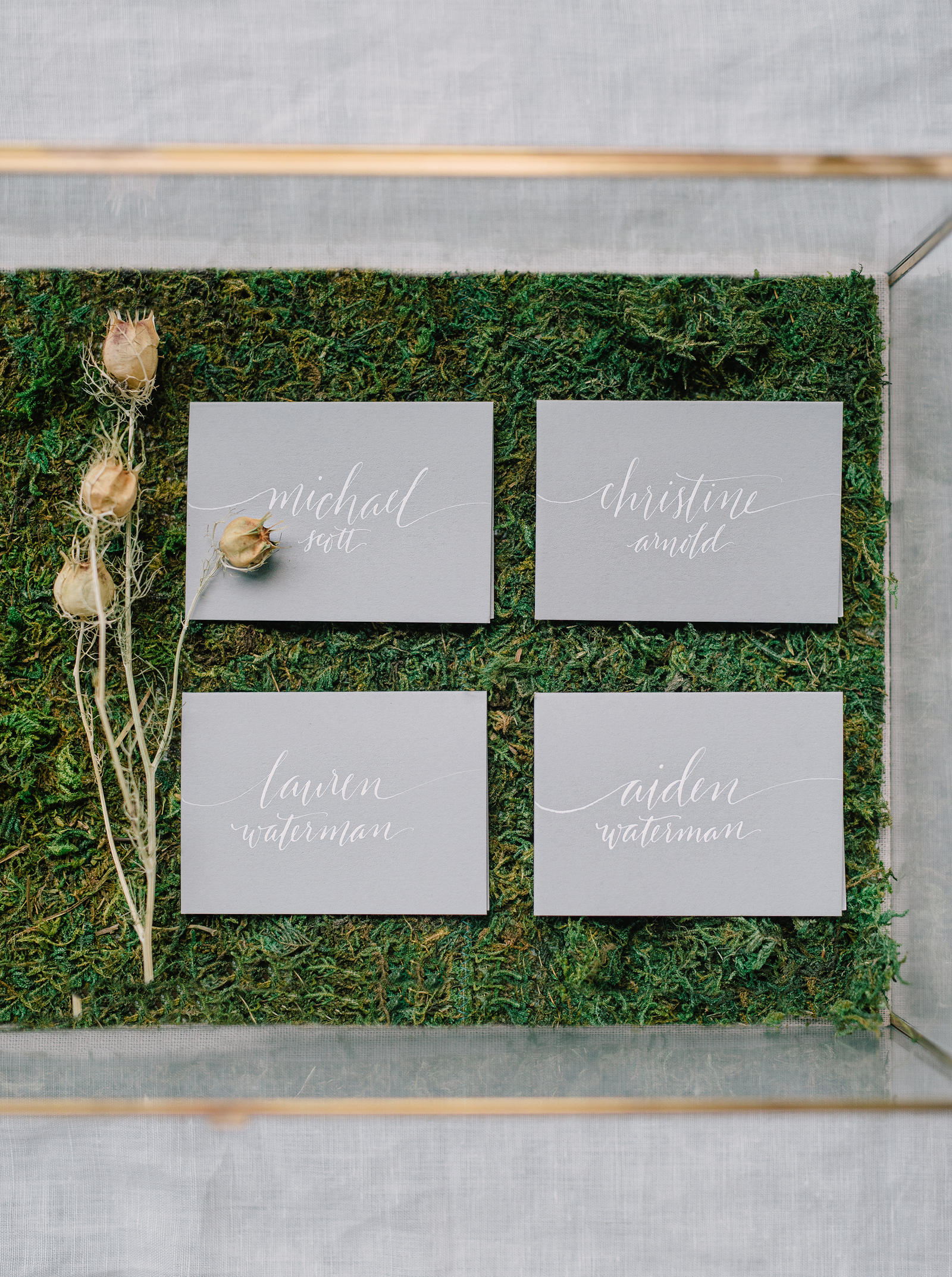 Editorial Photography | Atlanta, GA | Four namecards neatly arranged on a bed of moss.
