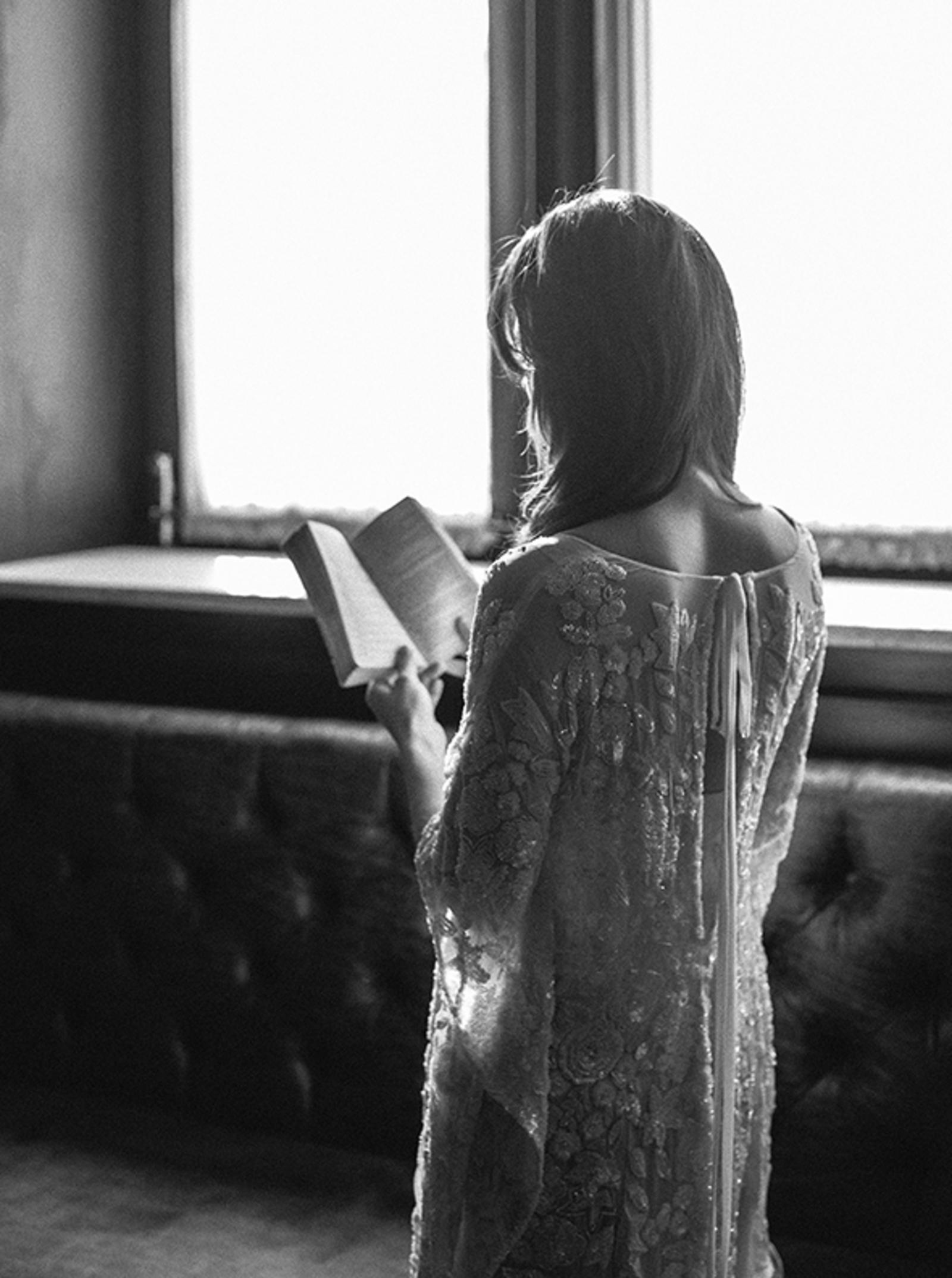 Editorial Photography | Atlanta, GA | A model in a simple wedding dress stands, reading a book.