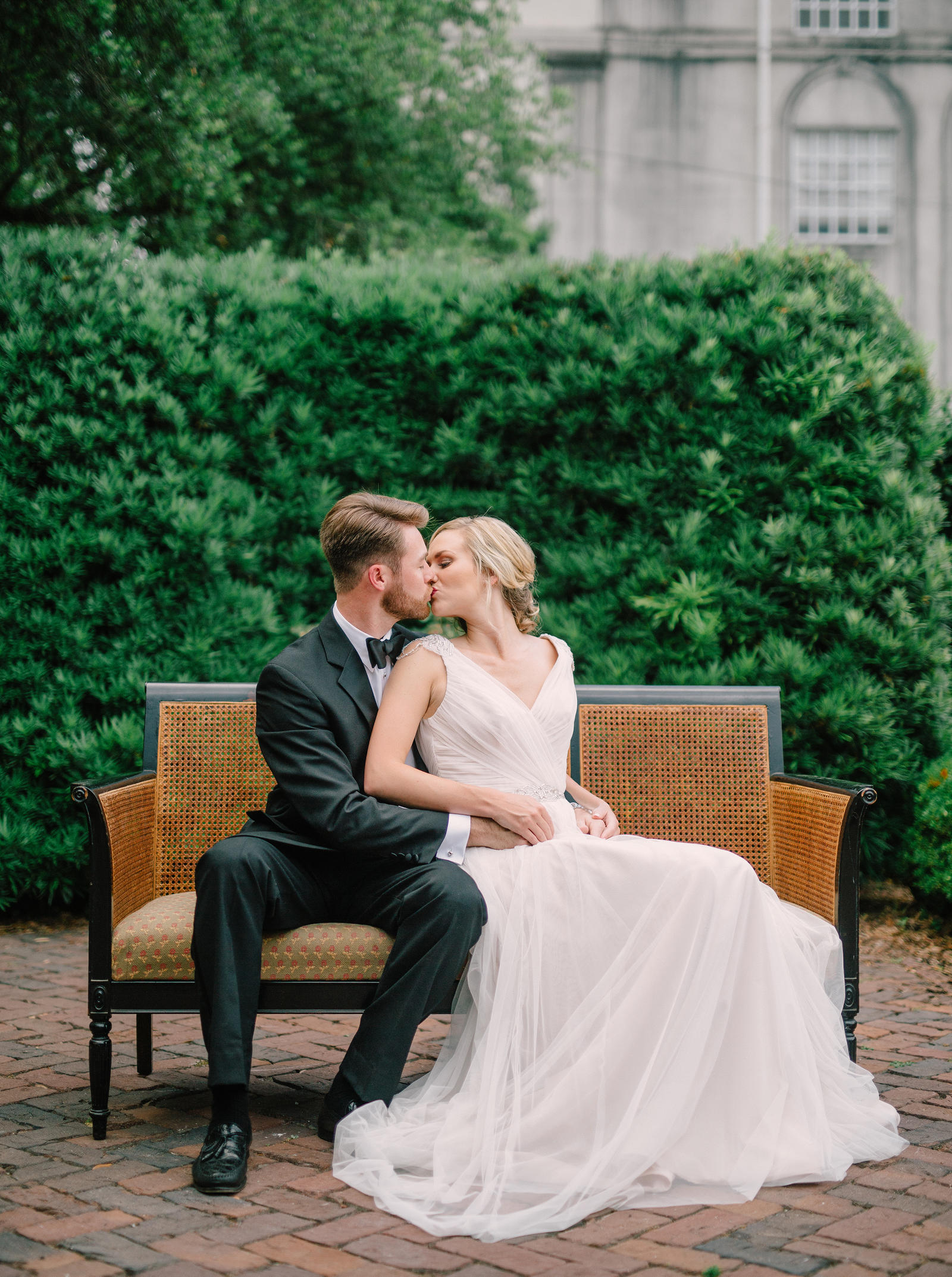 Editorial Photography | Atlanta, GA | A model bride and groom sit on a wicker bench in a courtyard, kissing.