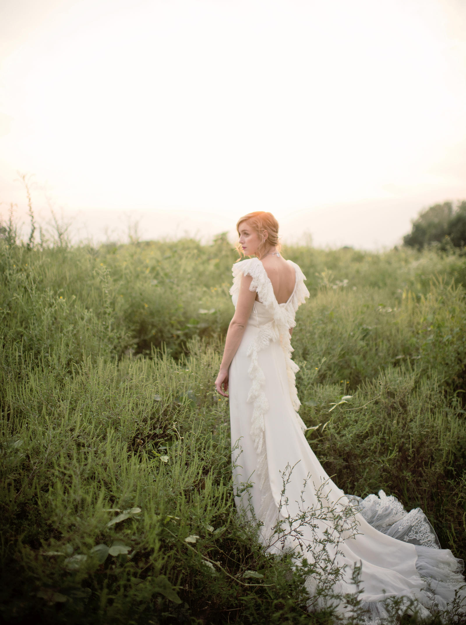 Editorial Photography | Atlanta, GA | A model in an elegant dress with a long train stands in an overgrown field.
