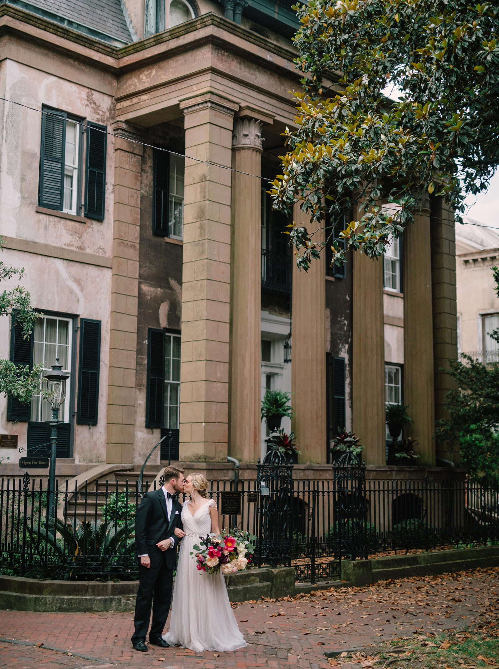 Editorial Photography | Atlanta, GA | A bride and groom stand, kissing, in front of a two story stone building that has large columns.