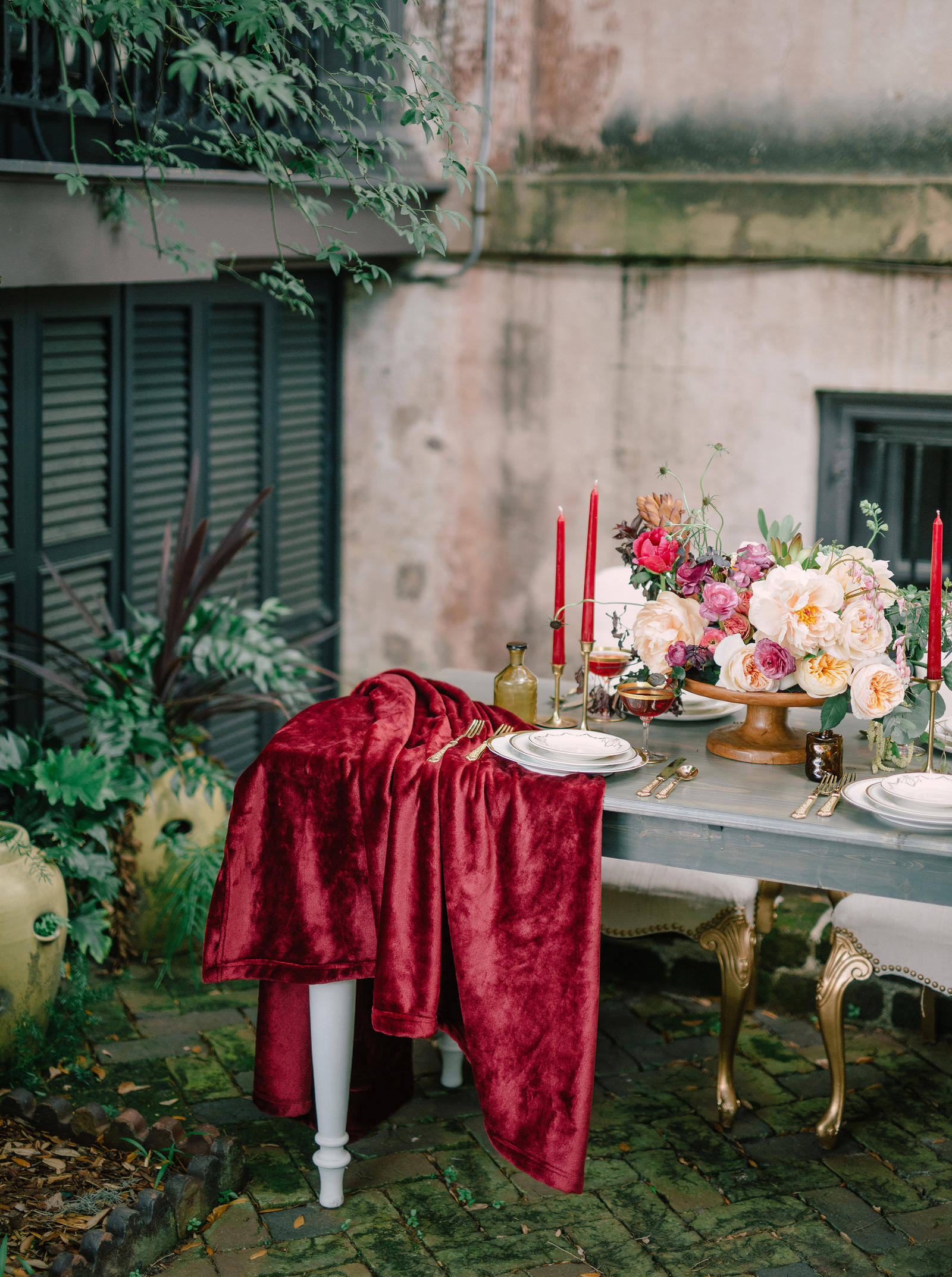Editorial Photography | Atlanta, GA | A place setting with a crushed red velvet table cloth draped over the side of the table.