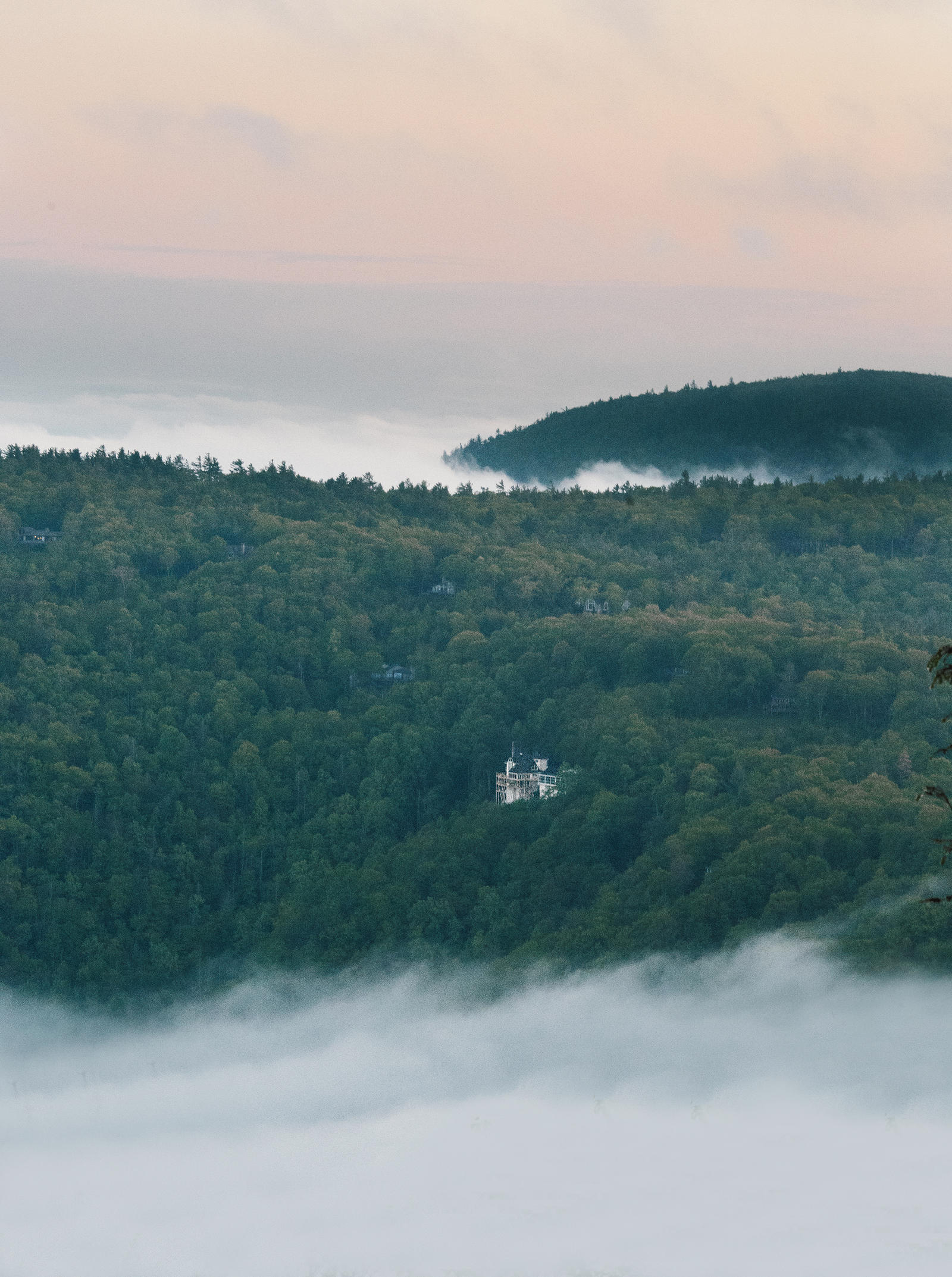 Lifestyle Photography | Atlanta, GA | A large hotel sits in a vast, wooded forest. Fog rolls into the valley.