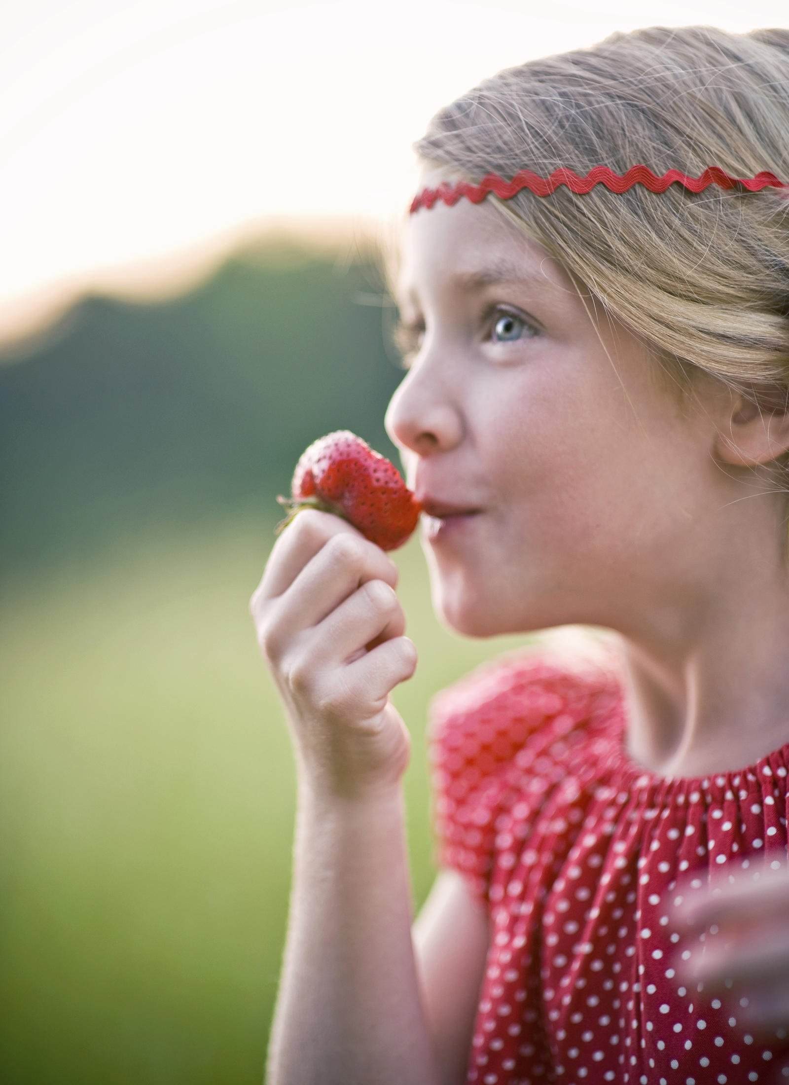 Lifestyle Photography | Atlanta, GA | Profile of a girl in a bright red dress eating a bright red strawberry.