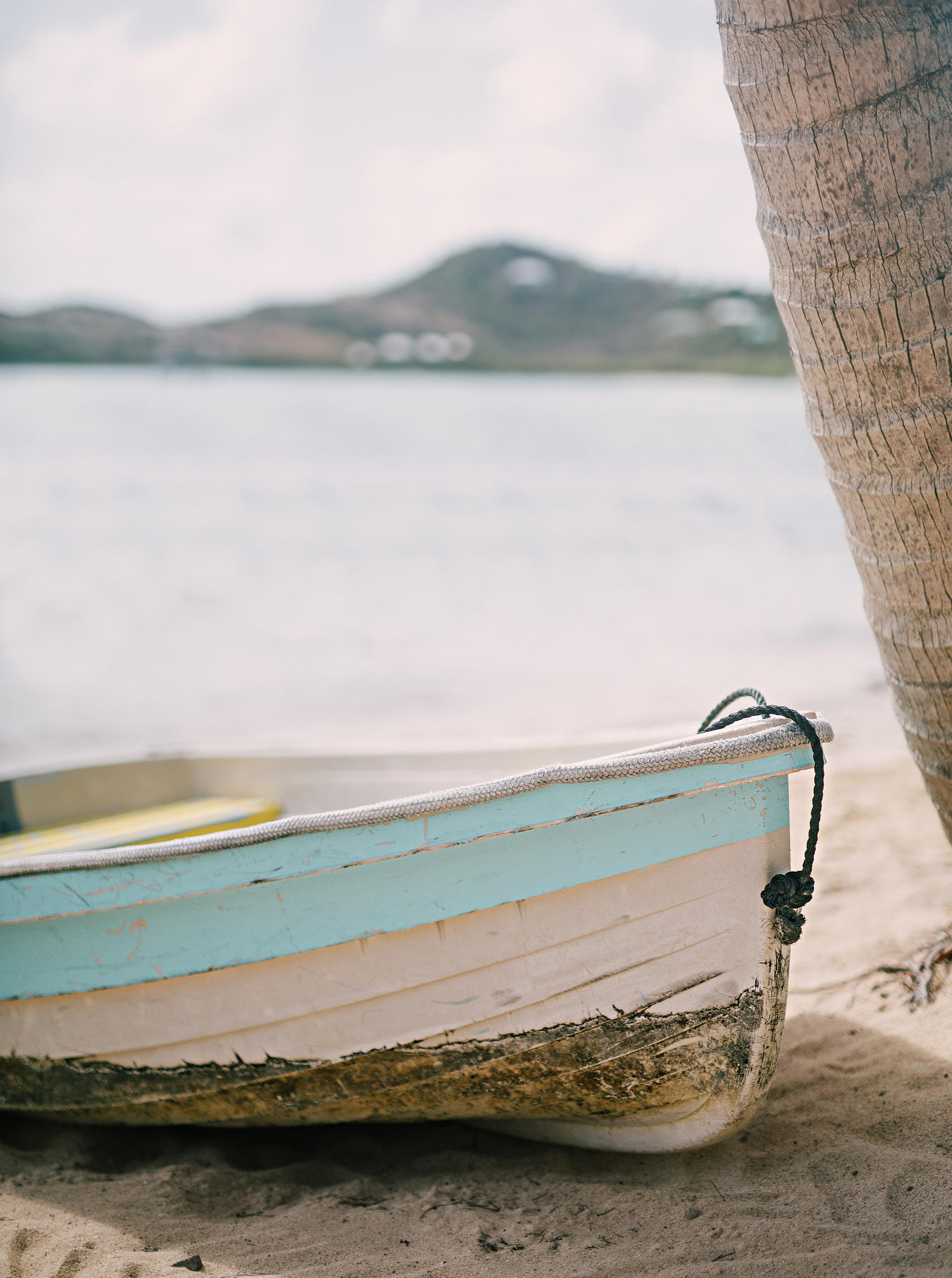 Atlanta Lifestyle Photography | Closeup of the bow of an old rowboat pulled onto the shore of the beach.