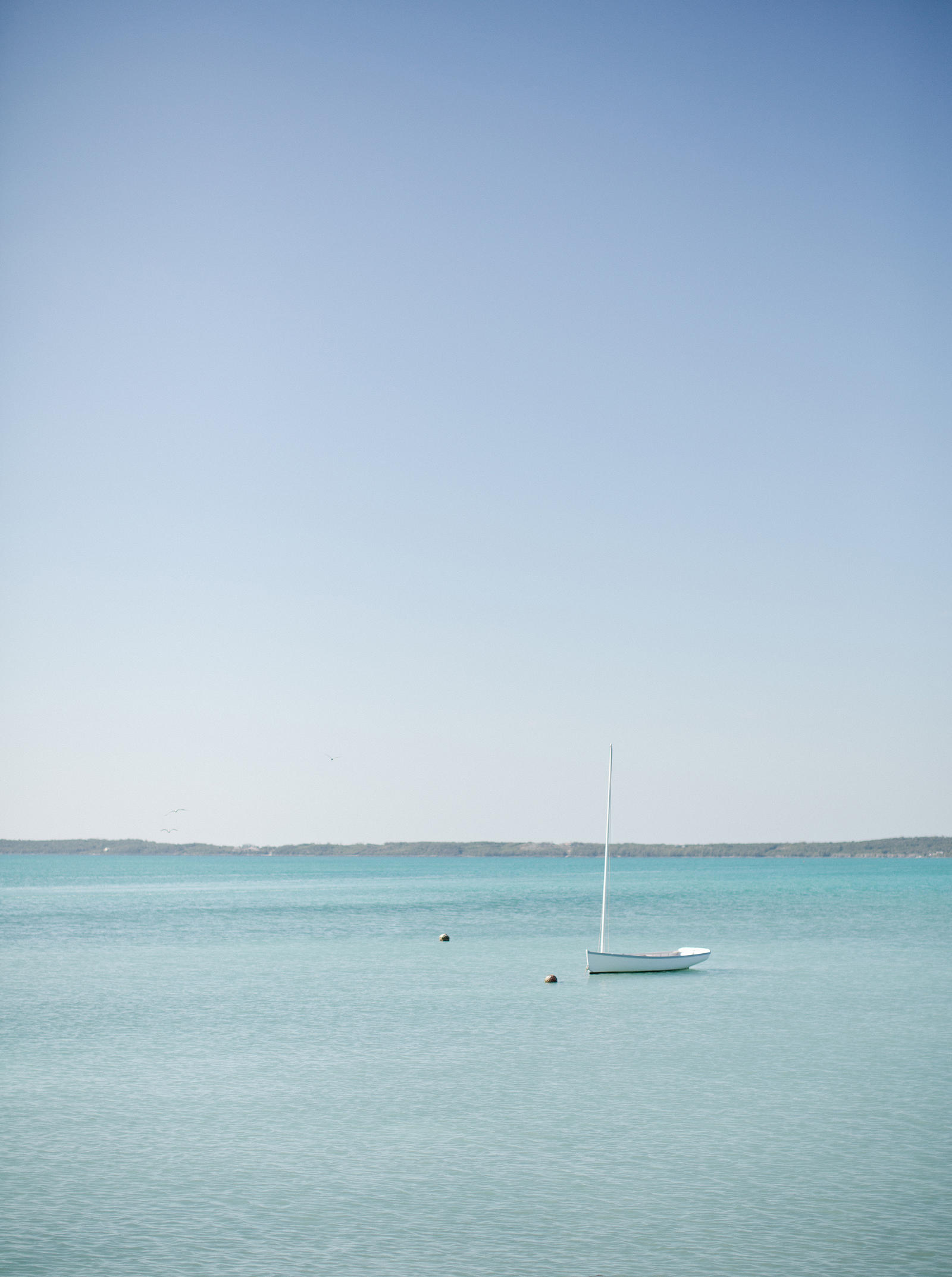 A small sailboat boat anchored in Harbour Island, Bahamas