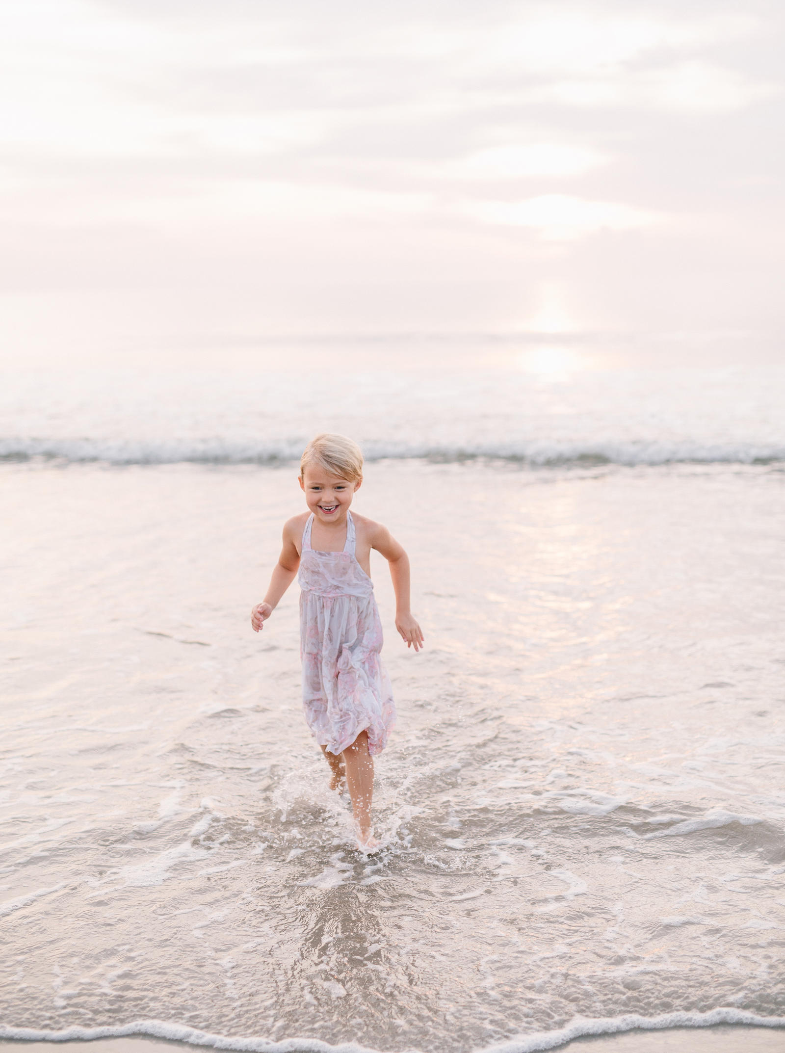 Atlanta Lifestyle Photography | A young child plays on the beach in shallow water.