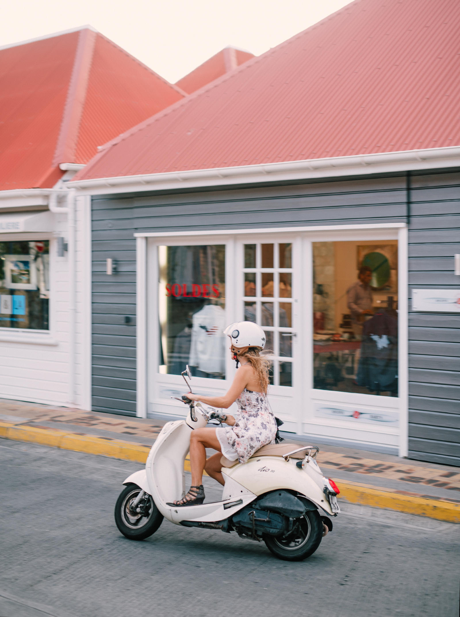 Lifestyle Photography | Atlanta, GA | A woman rides a Vespa scooter down the street.