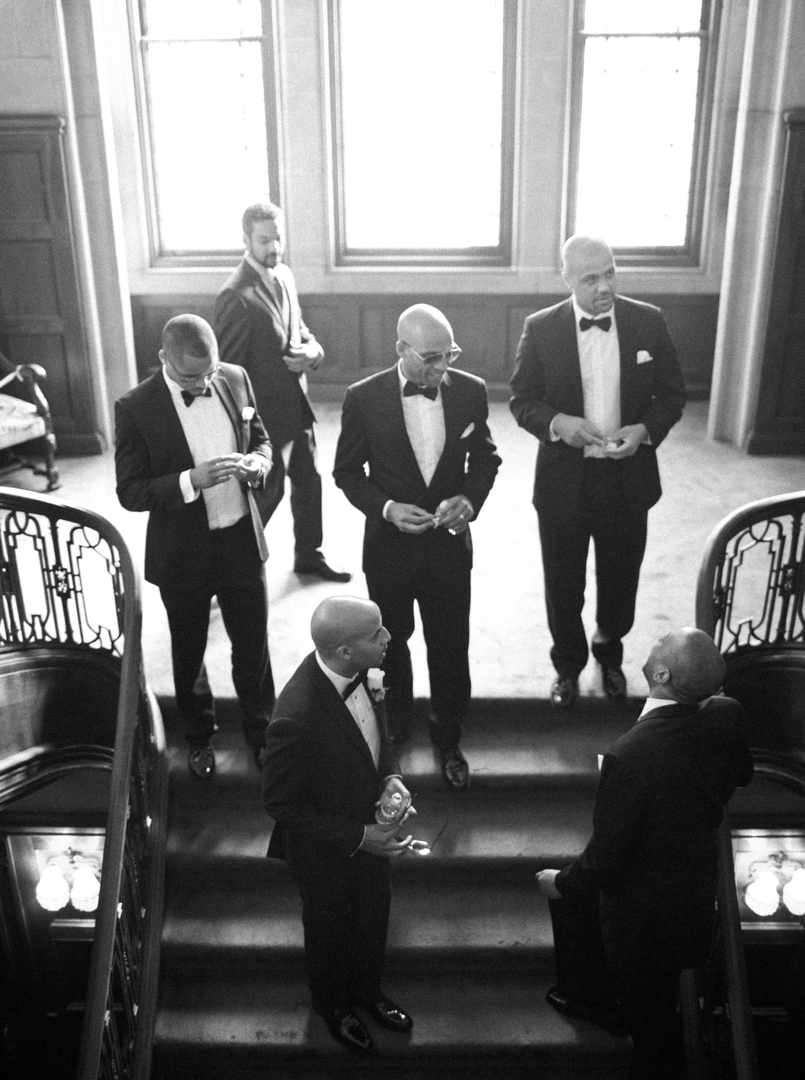 Wedding Photography | A groom and his groomsmen stand at the top of a stairwell, sharing a moment before the wedding.