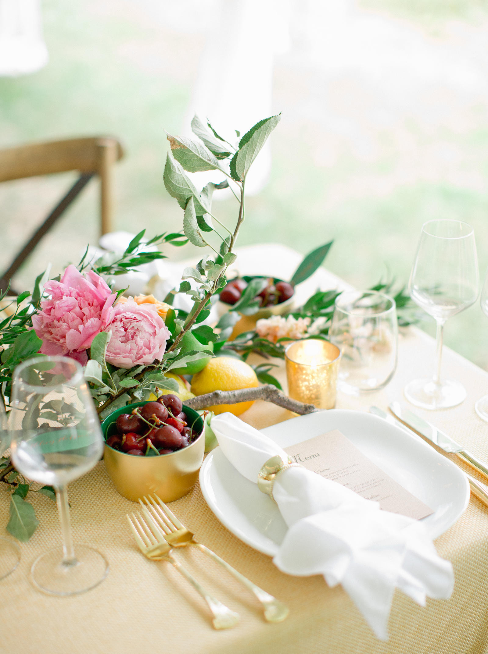 Wedding Photography | A place setting, with a floral, fruit arangement as the centerpiece.