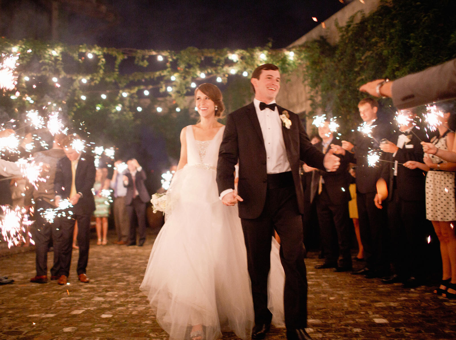 Wedding Photography | A bride and groom walk together as wedding guests wave sparklers.