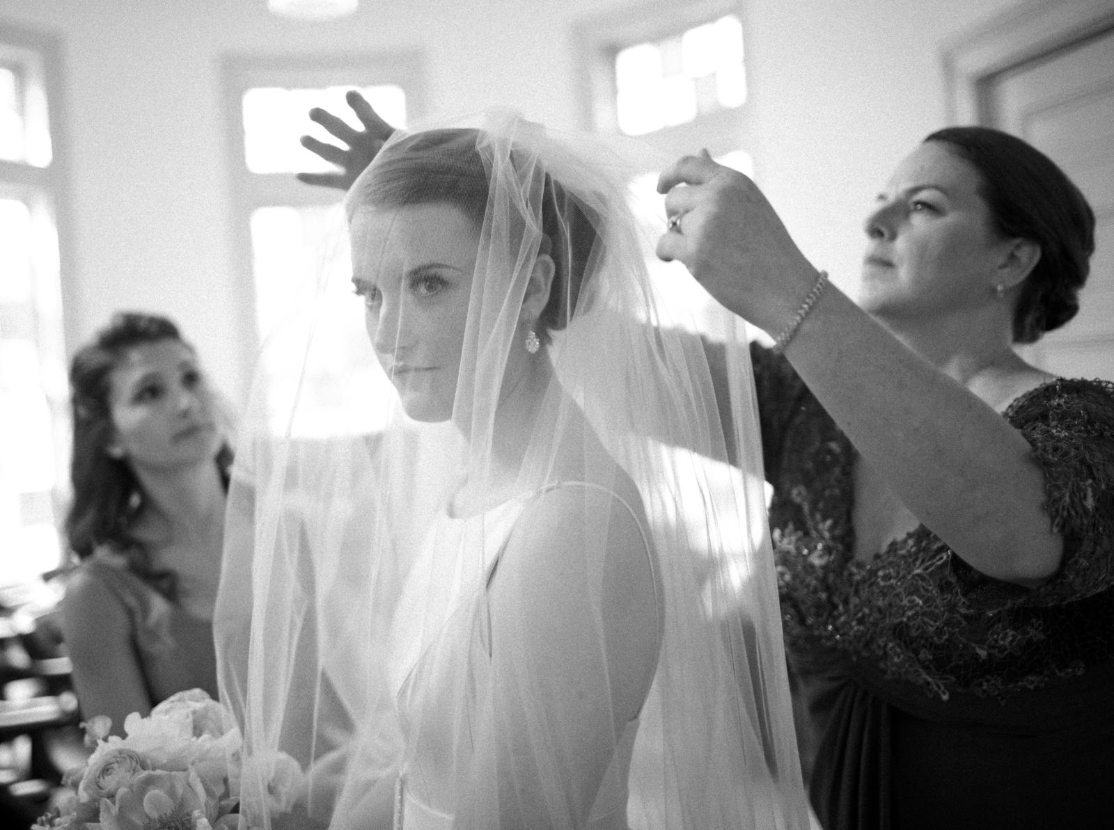 Wedding Photography | A bride has her veil fixed before the wedding ceremony.
