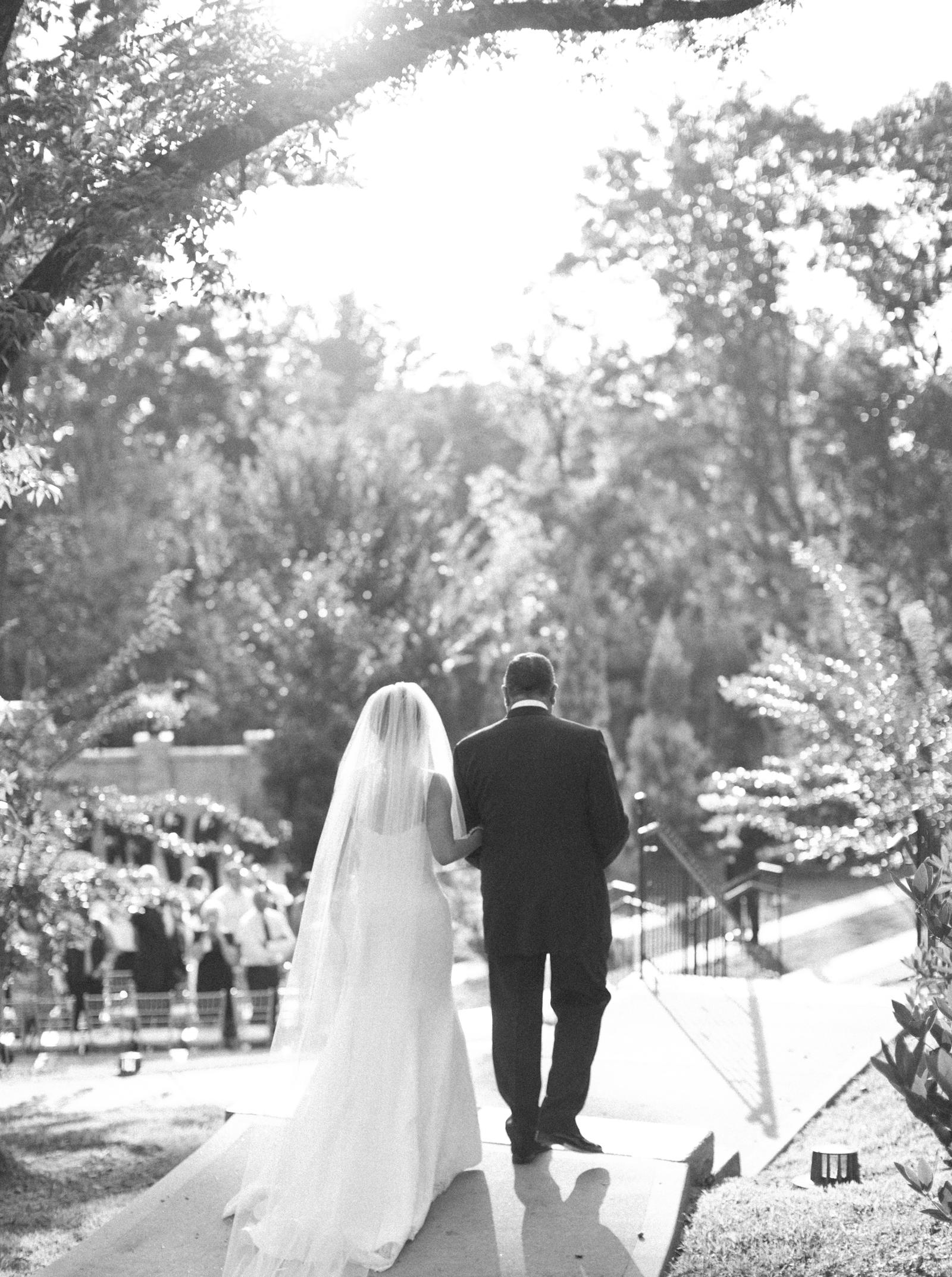 Wedding Photography | A bride and her father walk to the wedding ceremony, arm-in-arm.
