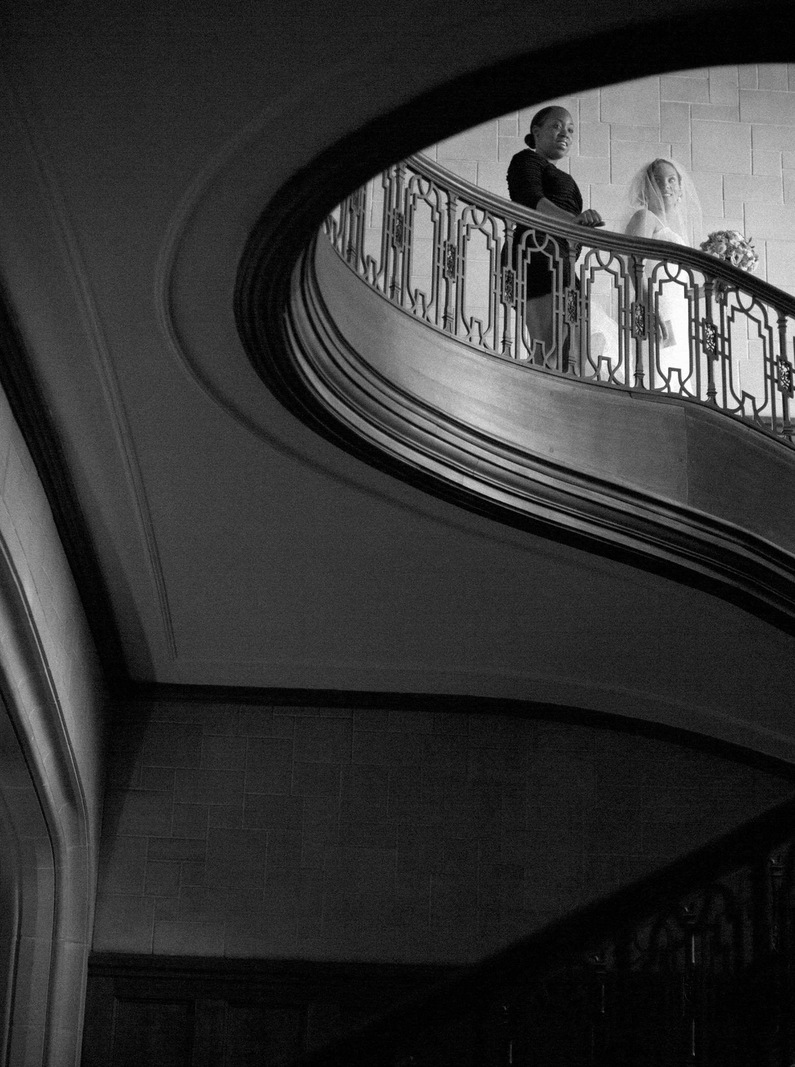 Wedding Photography | A bride decends the stairway, on the way to her wedding.