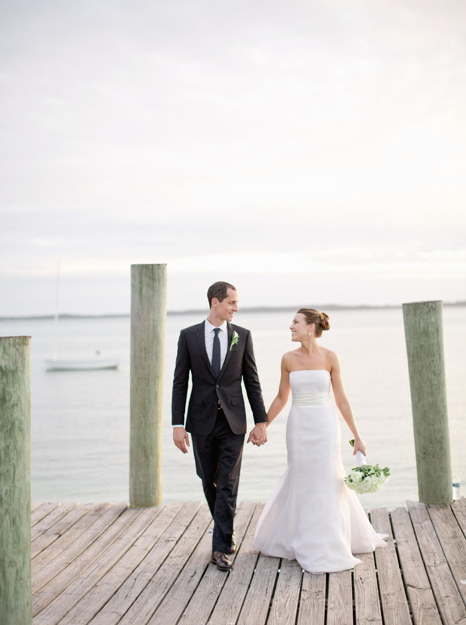 Wedding Photography | A bride and groom hold hands on a dock in Harbour Island, Bahamas