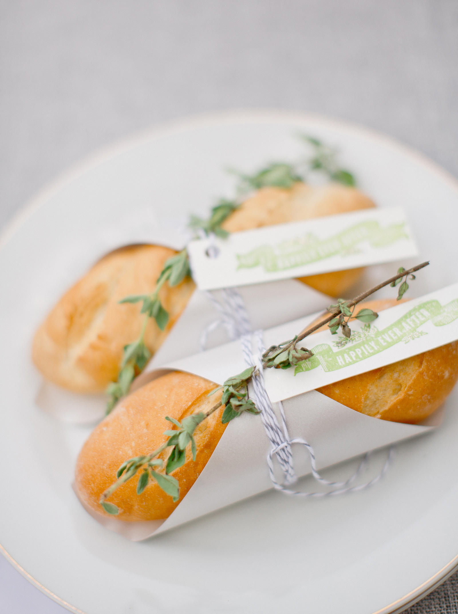 Wedding Photography | Small loaves of bread on a plate. A wedding message and herbs are tied to the bread.