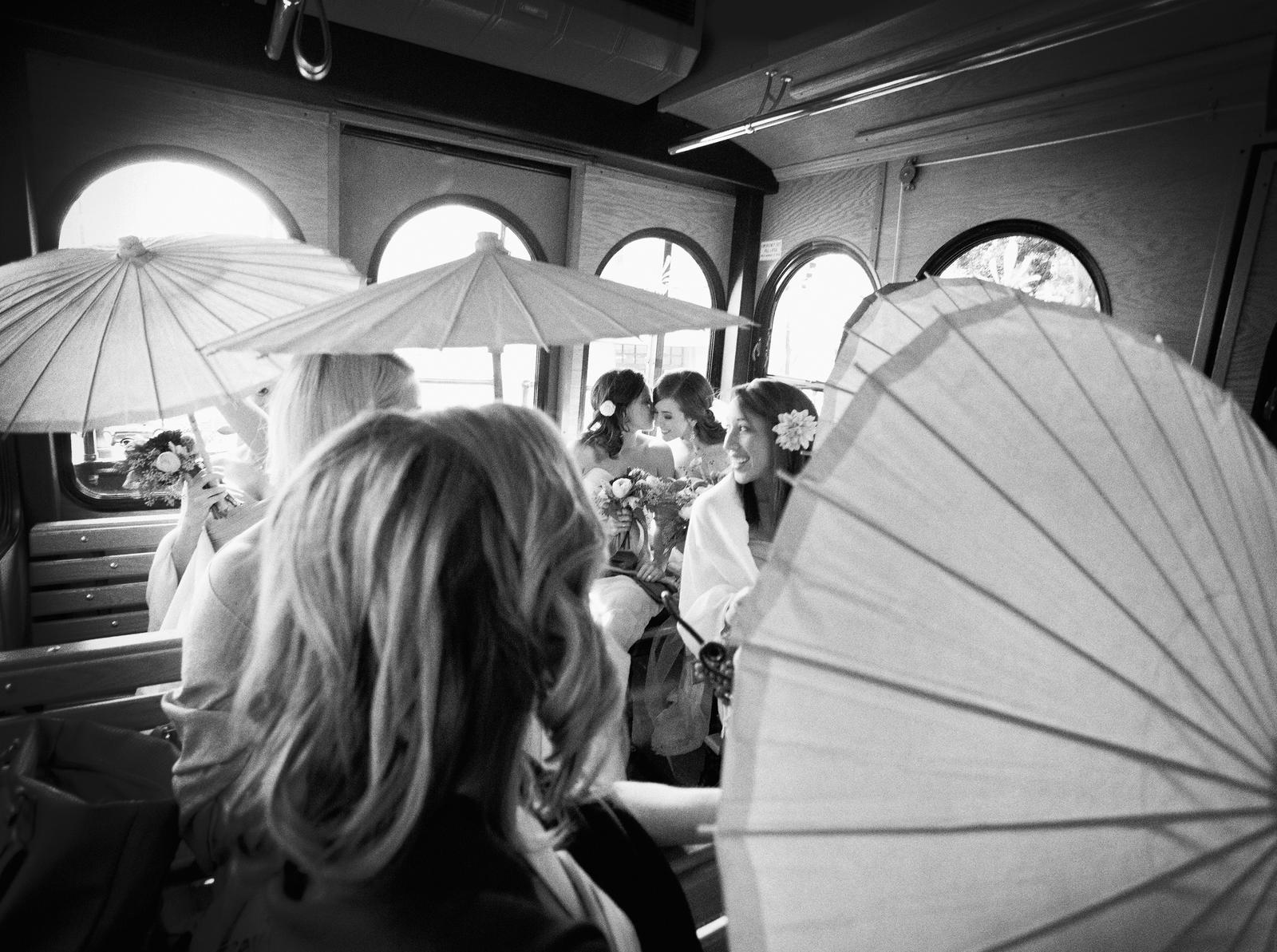Wedding Photography | A bride and her wedding party sit on a trolley, holding open parasols.