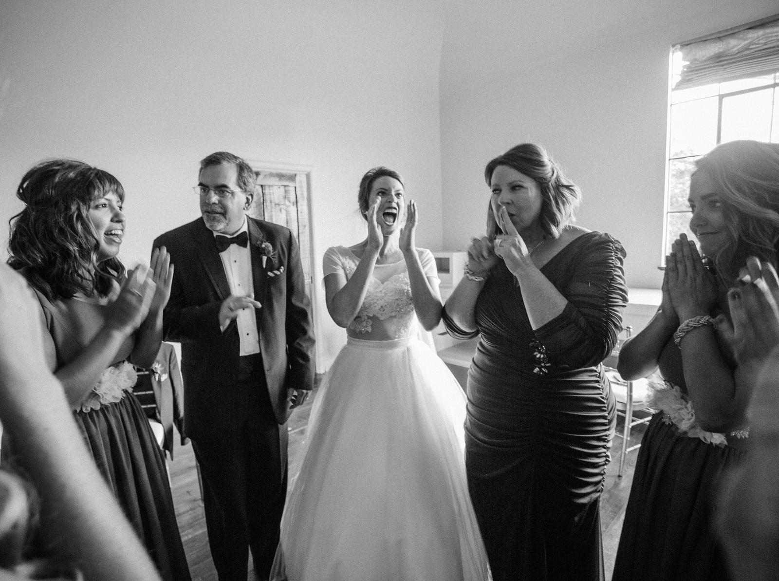 Wedding Photography | A bride, her mother and father and wedding party laughs before the wedding ceremony.