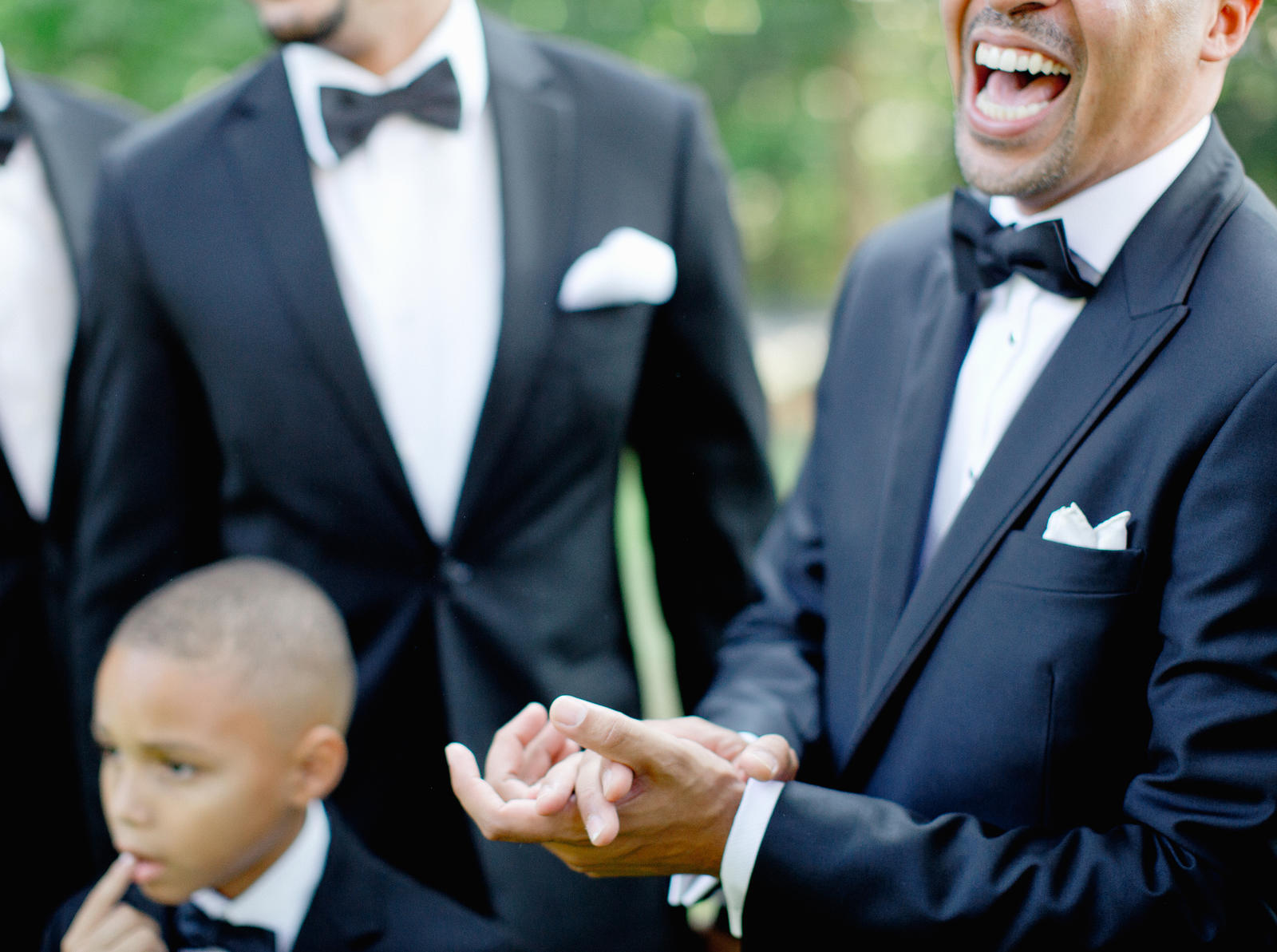 Wedding Photography | A groom and his groomsmen stand outside laughing.