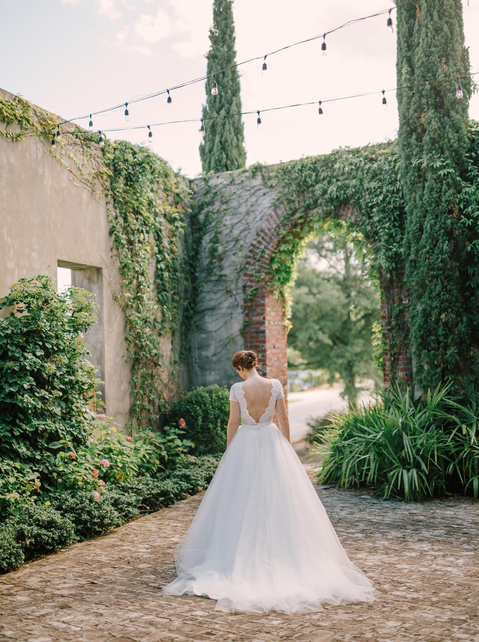 Wedding Photography | A bride stands in the courtyard with stringed lights over head.