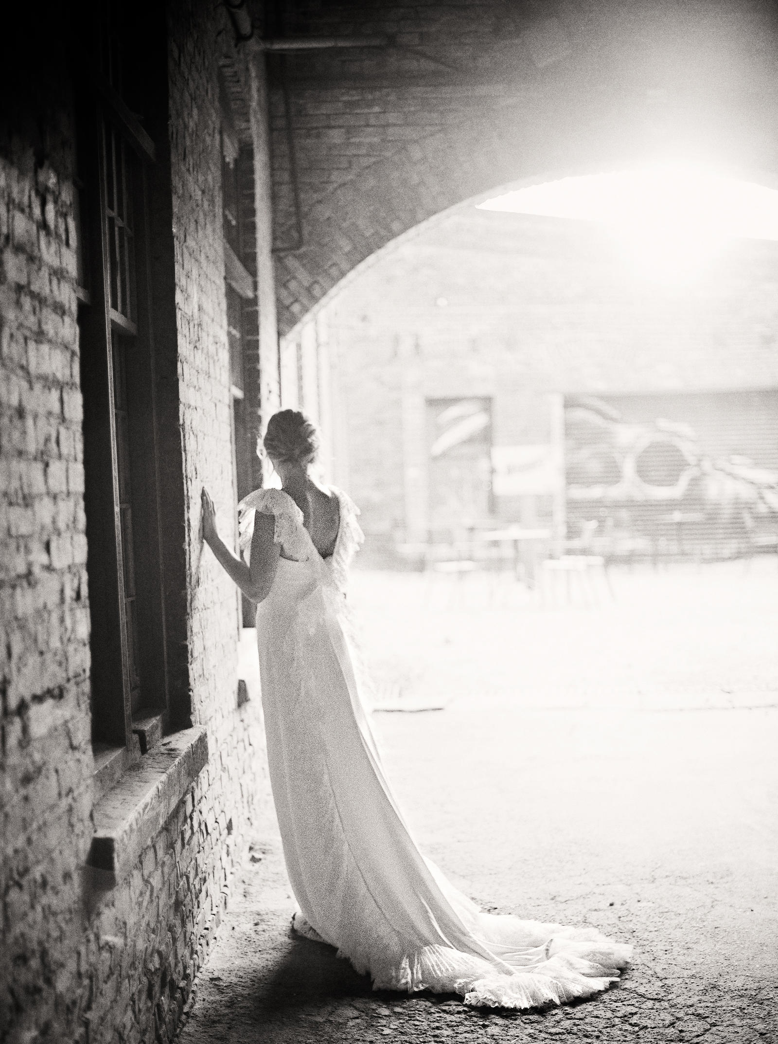 Wedding Photography | A bride looks out at a terrace, with her hand on a wall.