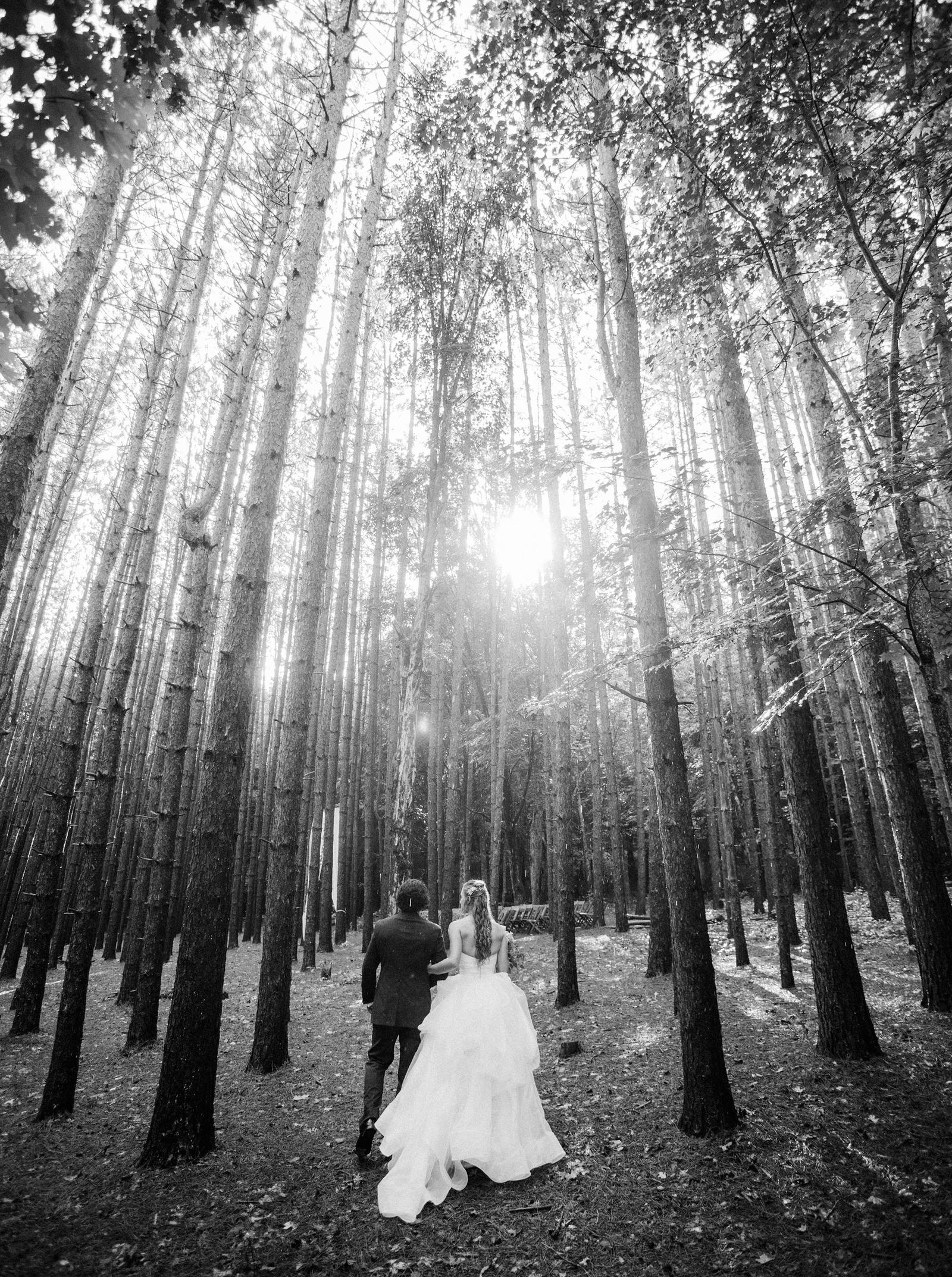 Wedding Photography | Bride and groom walk through the woods, the sun setting in the background.