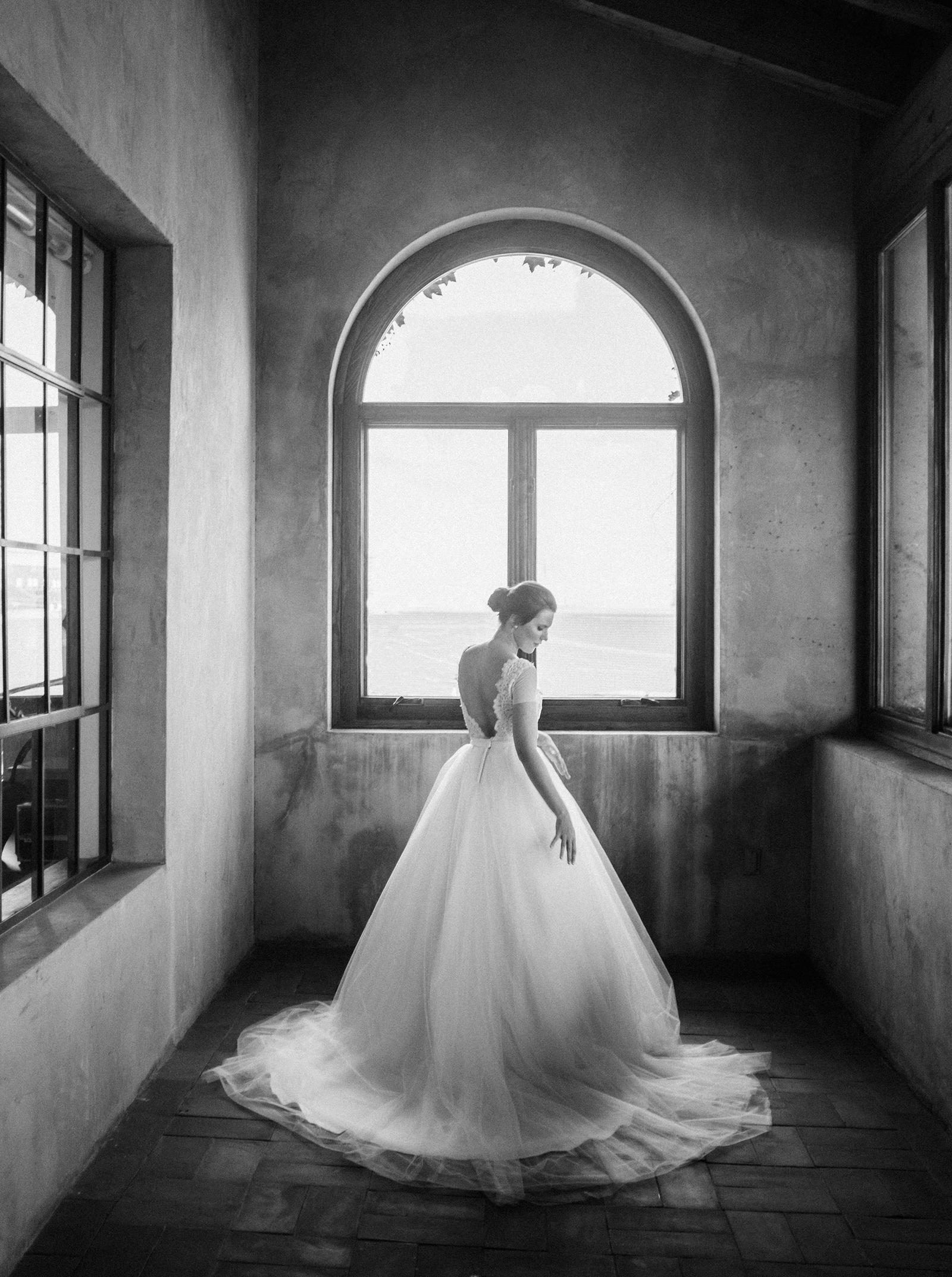 Wedding Photography | A bride stands in an alcove in front of a window.