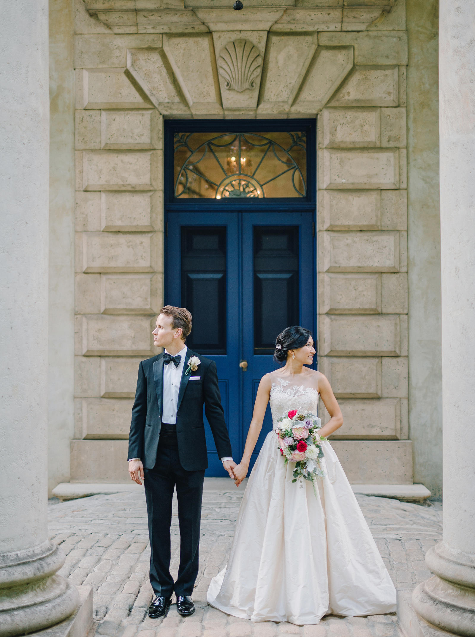 Wedding Photography | A bride and her groom stand under a portico, holding hands.