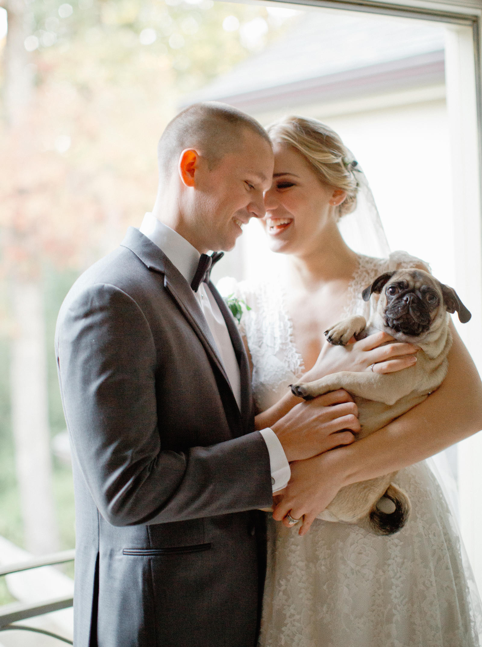 Wedding Photography | A bride and her groom share a laugh while holding their dog.