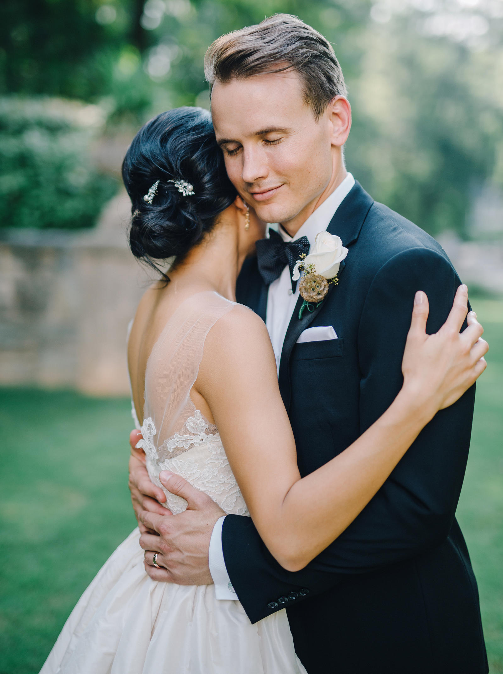 Wedding Photography | A bride and groom hold each other. The bride rests her head on the grooms shoulder.