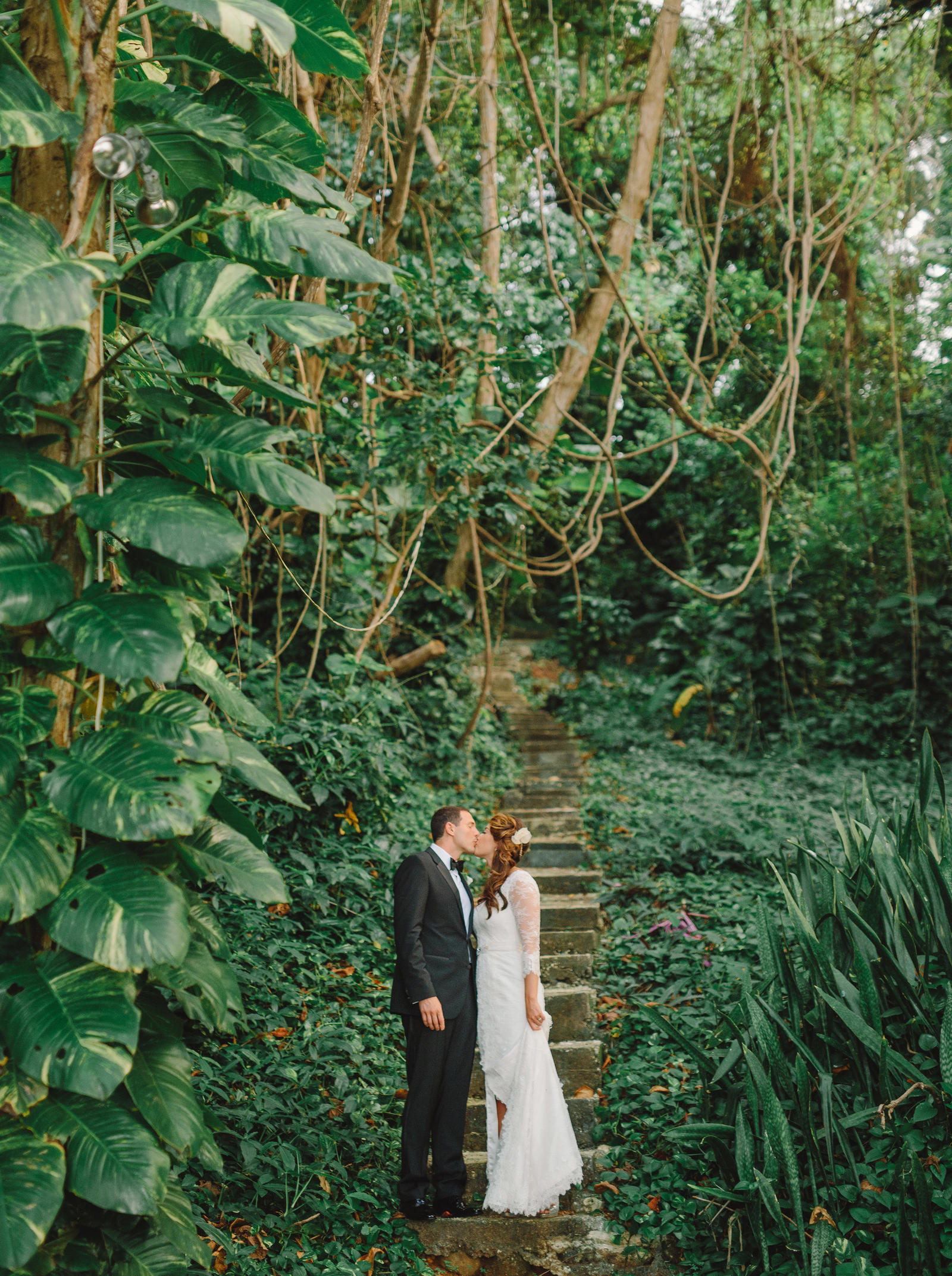 Wedding Photography | A bride and groom, kissing, on a stairway in a garden.