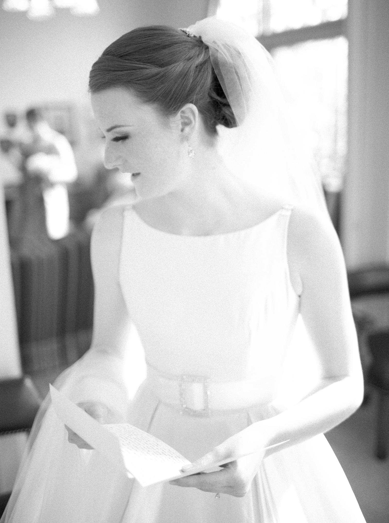 Wedding Photography | A bride reads a letter as she prepares for the wedding ceremony.