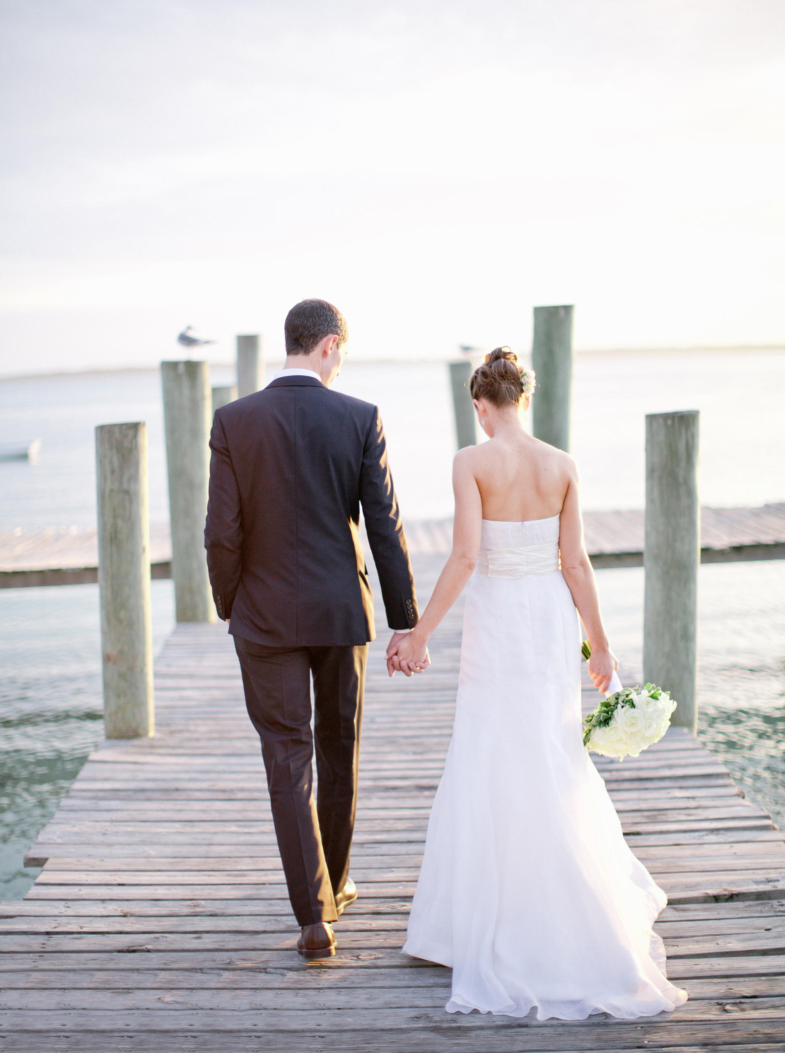 Wedding Photography | Bride and groom walk hand-in-hand on a dock in Harbour Island Bahamas