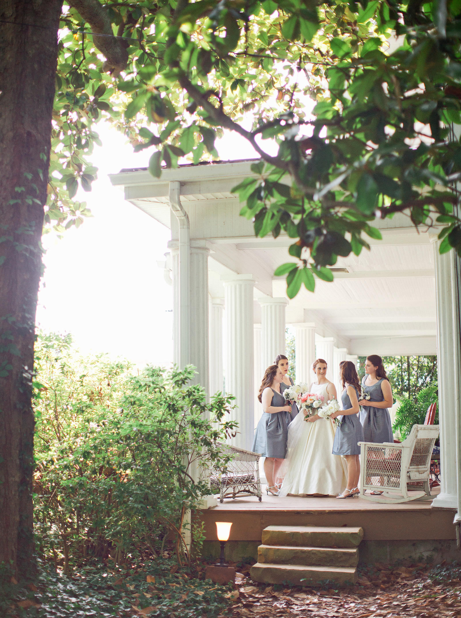 Wedding Photography | A bride and her wedding party share a laugh, standing on a porch.