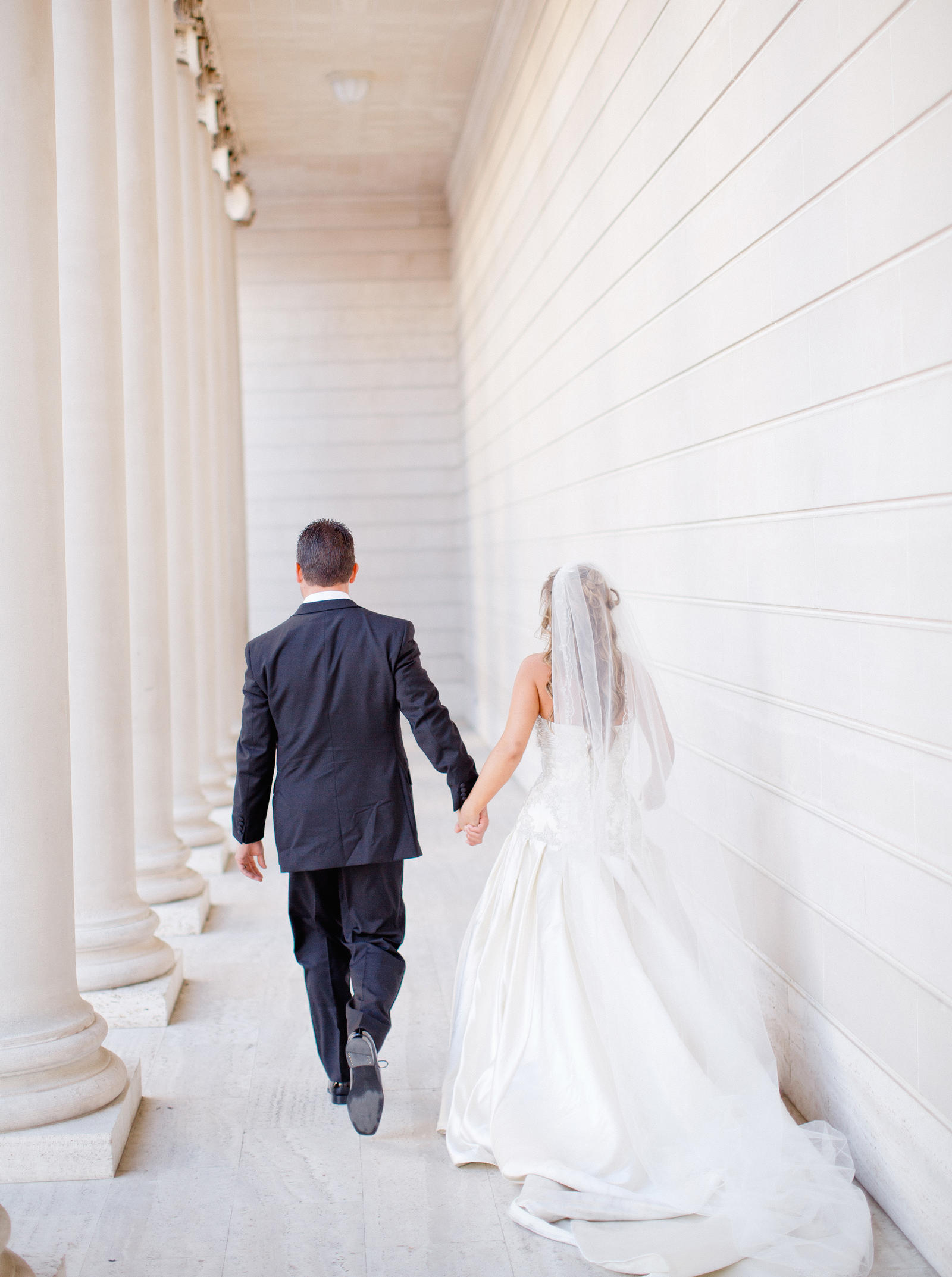 Wedding Photography | A bride and groom walk hand-in-hand down a walkway.