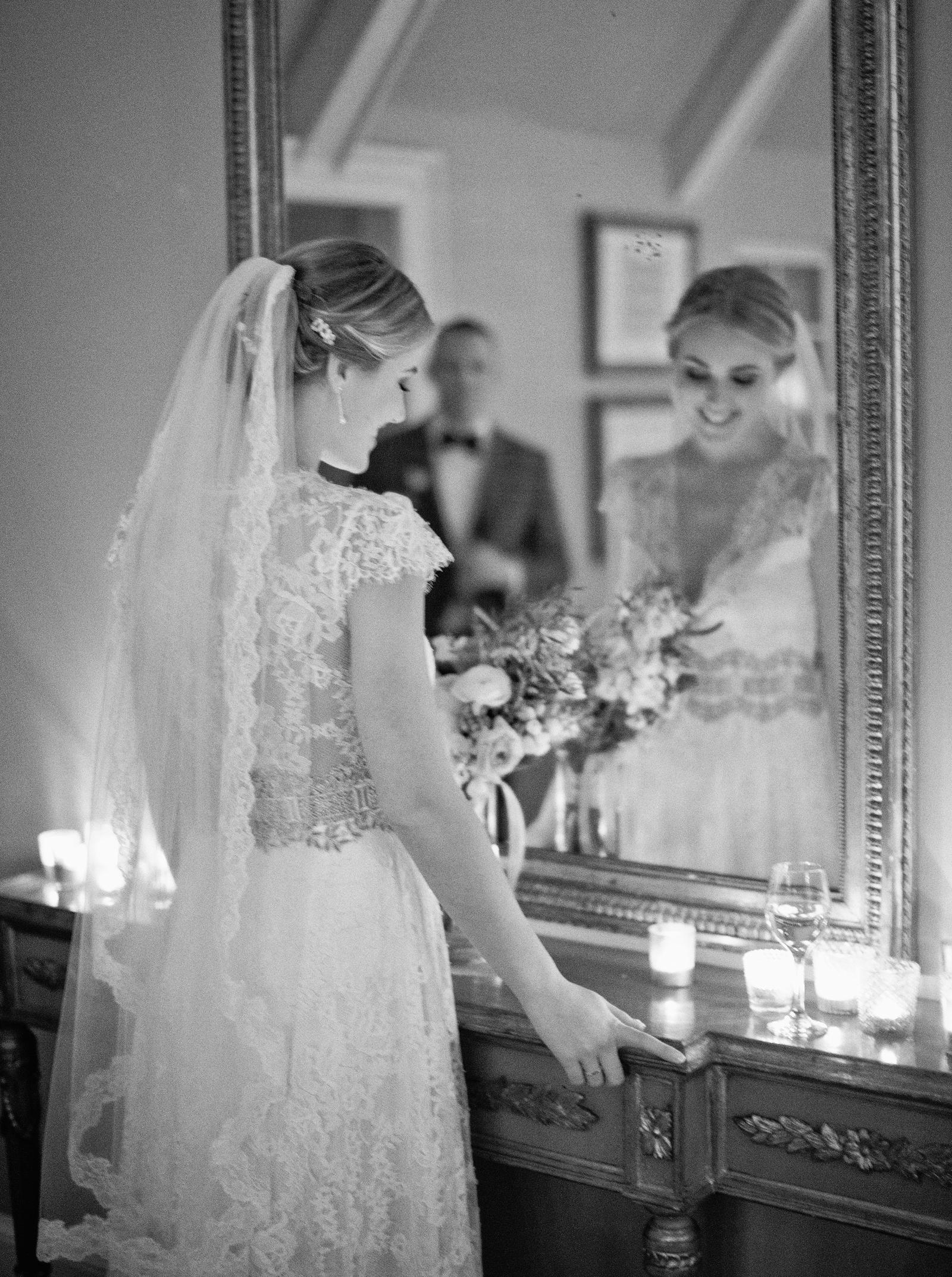 Wedding Photography | A bride stands in front of a mirror, her groom's reflection can be seen.