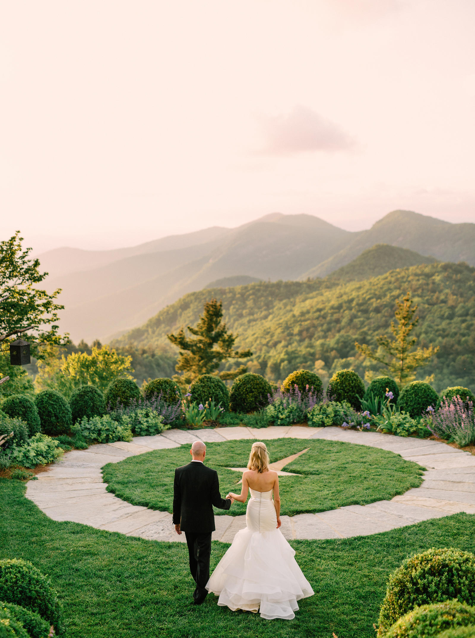 Wedding Photography | A bride and groom walk out into a garden courtyard, overlooking mountains in the distance.